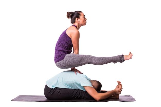 Jeune couple en bonne santé homme et femme en position d'yoga sur fond blanc