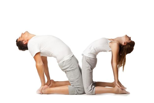 Jeune couple en bonne santé en position de yoga sur fond blanc