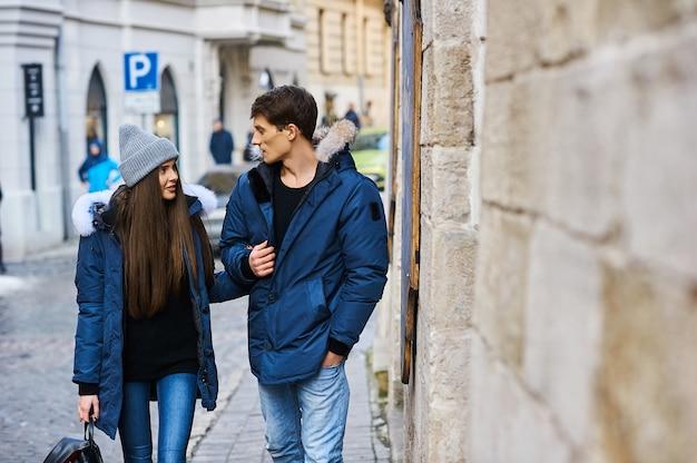 Un jeune couple branché se promène dans la ville à noël