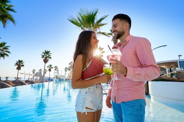 Jeune couple buvant un cocktail au bord de la piscine