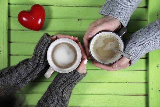Jeune couple buvant du café chaud à une table en bois à une date