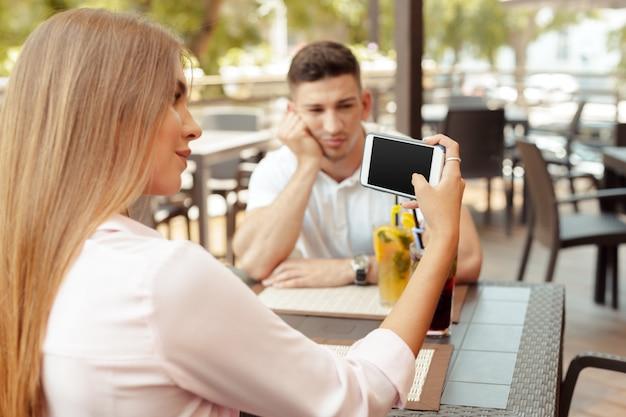 Jeune couple buvant du café dans un café. homme sérieux regardant avec inquiétude pendant que sa fille utilise un téléphone intelligent