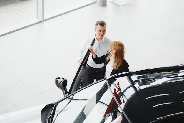 Jeune couple byuing une voiture dans une salle d'exposition de voiture