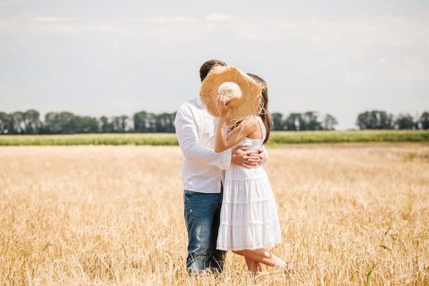 Jeune couple, cacher, chapeau