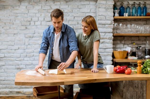 Jeune couple, caking, pizza, dans, cuisine, ensemble