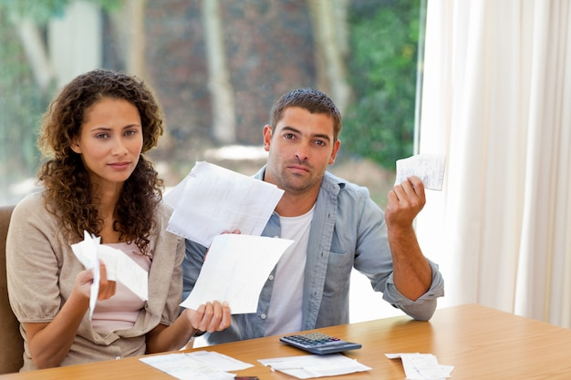 Jeune couple calculant leurs factures domestiques