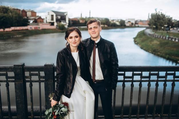 Jeune couple câlins sur un pont sur une rivière. la mariée et le marié dans des vestes en cuir. couple d'amoureux par une froide journée d'automne à pied dans la ville. panorama de la ville avec un ciel d'orage