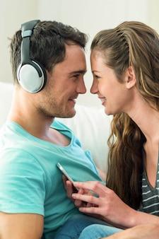 Jeune couple câlins tout en écoutant de la musique sur téléphone portable dans le salon