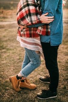 Jeune couple caresses au coucher du soleil dans les montagnes. photos sans visages. gros plan des mains. l'homme et la femme sont vêtus de vêtements en jean et de chaussures rouges, de baskets noires. concept de relation solide