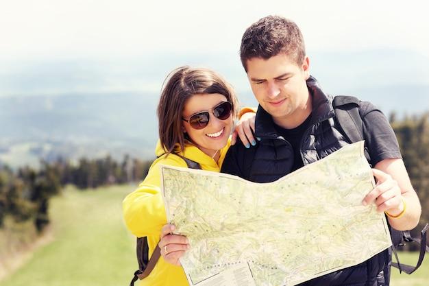 Un jeune couple avec une carte dans les montagnes en pologne