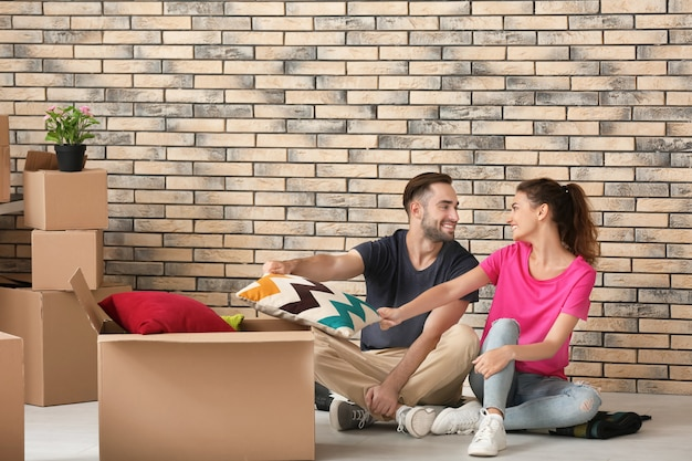 Jeune couple avec des cartons de déménagement à la nouvelle maison