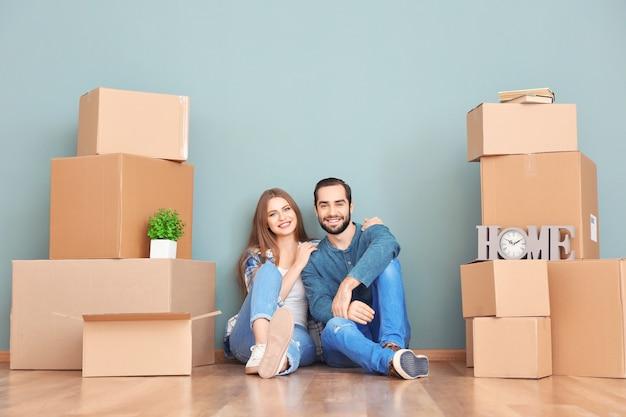 Jeune couple avec des cartons de déménagement sur le sol dans la chambre