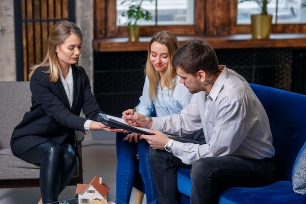 Jeune couple caucasien assis sur l'entraîneur pendant que l'homme signe le contrat d'achat d'une nouvelle maison, appartement.
