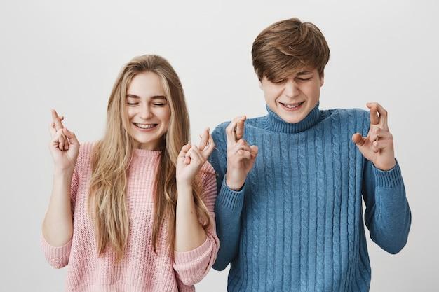 Jeune couple caucasien aux yeux fermés, fronçant les sourcils et croiser les doigts souhaitant quelque chose qui pose contre l'espace gris