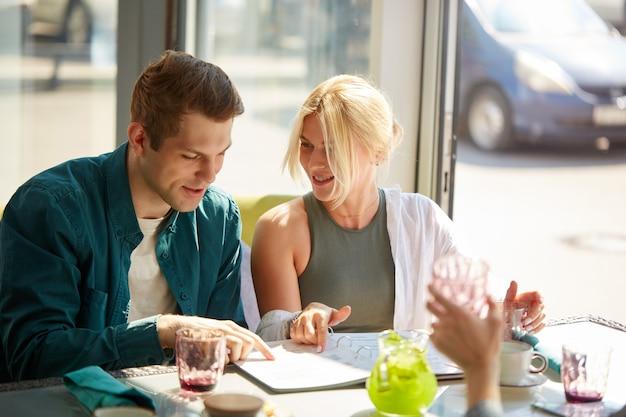 Jeune couple caucasien choisit le repas dans le menu ensemble