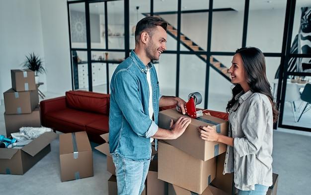 Jeune couple caucasien emballage boîte en carton pour se déplacer dans un nouvel appartement.