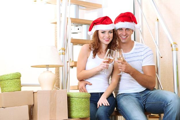 Jeune couple célébrant le nouvel an dans une nouvelle maison sur fond d'escaliers
