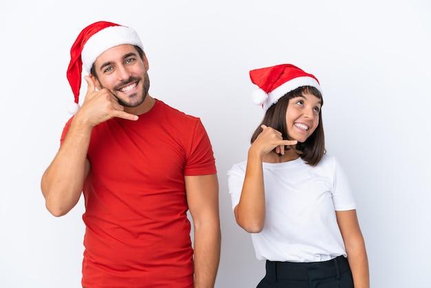Jeune couple avec chapeau de noël isolé sur fond blanc faisant le geste du téléphone. rappelle-moi signe