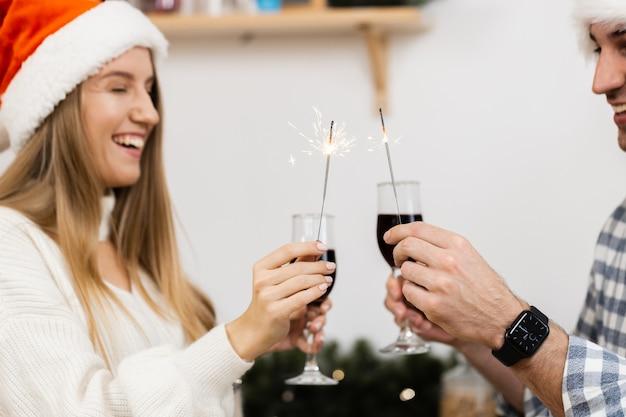 Jeune couple en chapeaux de père noël buvant du vin et célébrant noël, gros plan