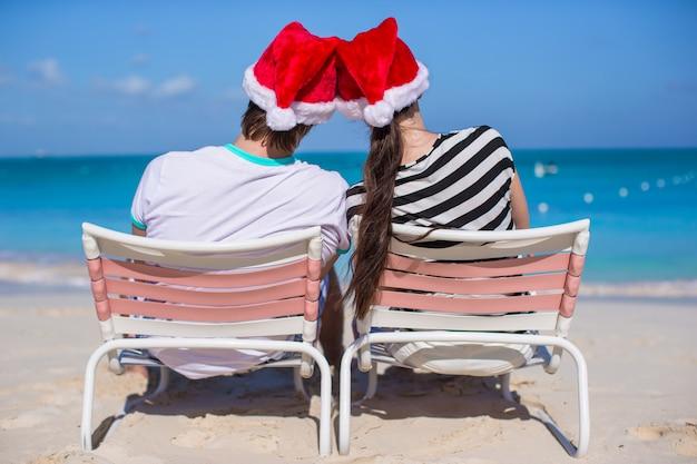 Jeune couple en chapeaux santa profiter de vacances à la plage