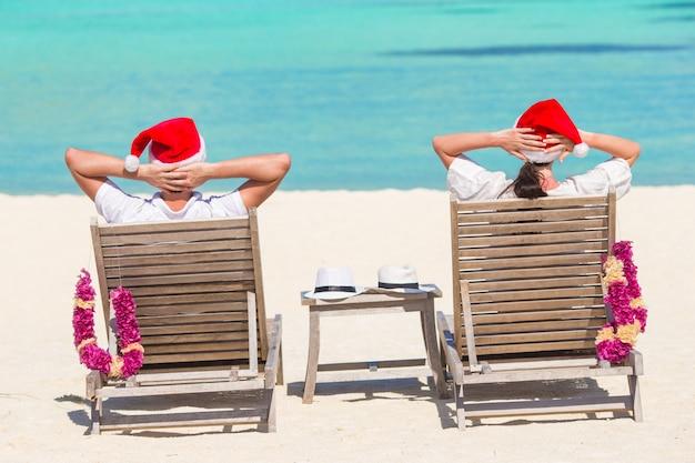 Jeune couple en chapeaux santa se détendre sur une plage tropicale pendant les vacances de noël