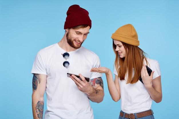 Jeune couple en chapeaux avec des téléphones en mains communication de mode