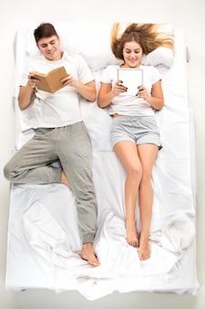 Le jeune couple charmant allongé dans un lit avec des livres
