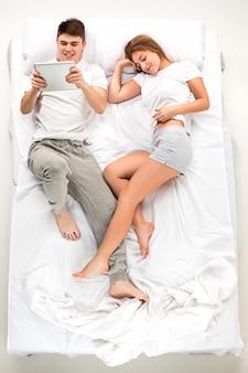 Le jeune couple charmant allongé dans un lit avec ordinateur portable
