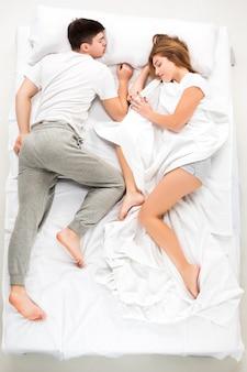 Le jeune couple charmant allongé dans un lit