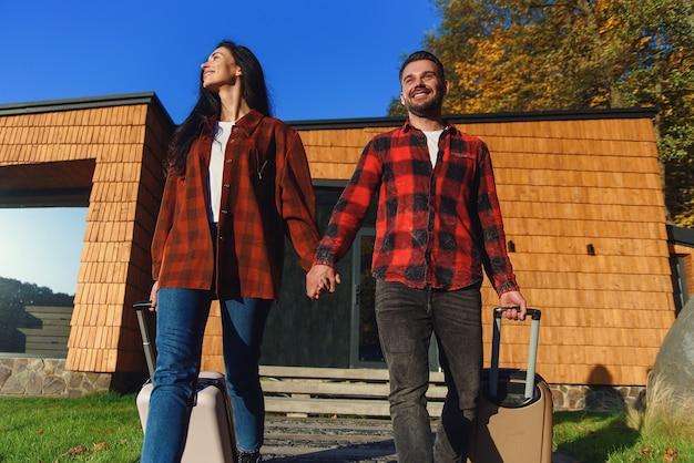 Jeune couple charmant caucasien avec des bagages quittant la maison pour les vacances. concept de famille heureuse.