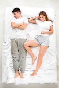 Le jeune couple charmant couché dans un lit