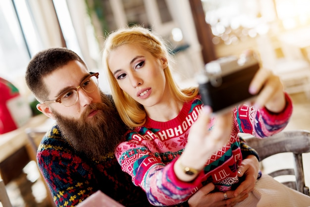 Jeune couple charmant dans un pull étreignant et prenant un selfie