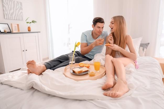 Jeune couple charmant prenant son petit déjeuner sur le lit