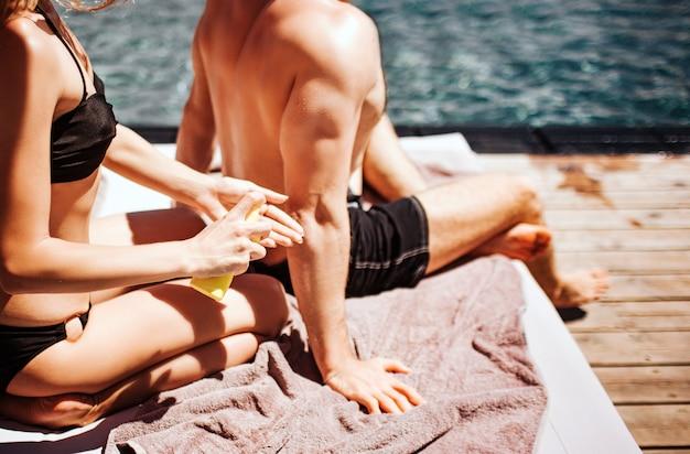 Jeune couple chaud au repos à la piscine