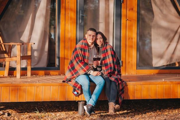 Jeune couple sur la chaude journée d'automne sur la terrasse de leur maison