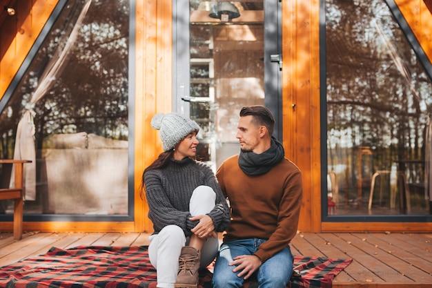 Jeune couple à la chaude journée d'automne sur la terrasse de leur maison