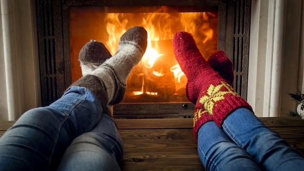 Jeune couple en chaussettes tricotées chaudes se détendre dans un chalet au foyer