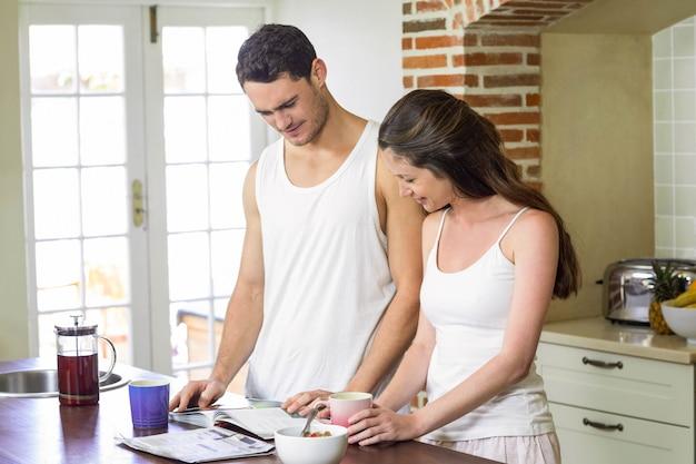 Jeune couple cherche son organisateur personnel tout en prenant son petit déjeuner dans la cuisine