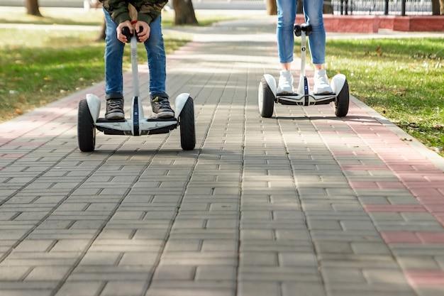 Un jeune couple chevauchant un hoverboard dans un parc