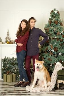 Jeune couple avec un chien couchait autour de l'arbre de noël