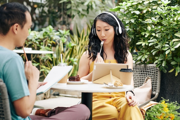 Jeune couple chinois mangeant des desserts au café, regardant des webinaires et travaillant sur des projets pour l'université ou le collège