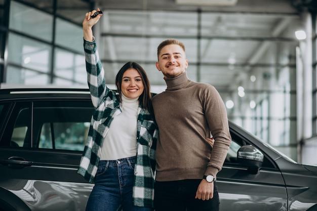 Jeune couple, choisir, a, voiture, dans, a, exposition voiture, salle