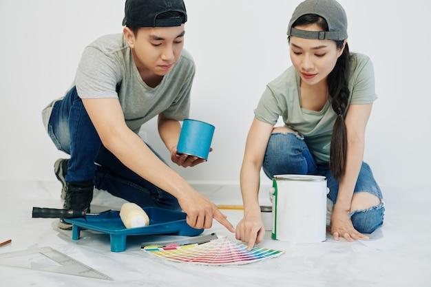 Jeune couple choisissant la couleur des murs