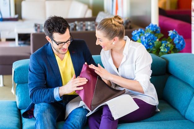 Jeune couple choisissant ensemble housse de siège pour canapé dans un magasin de meubles
