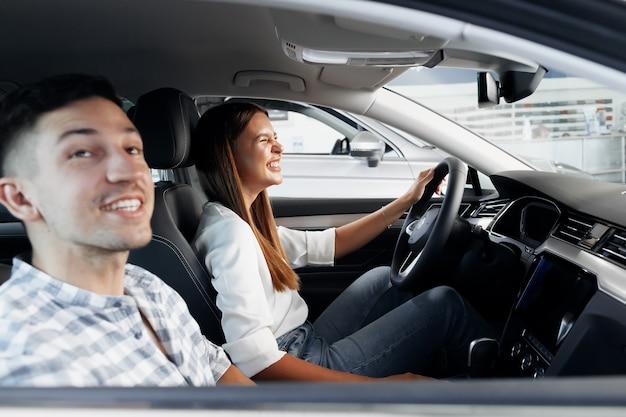 Jeune couple choisissant leur nouvelle voiture dans un magasin de voiture ensemble