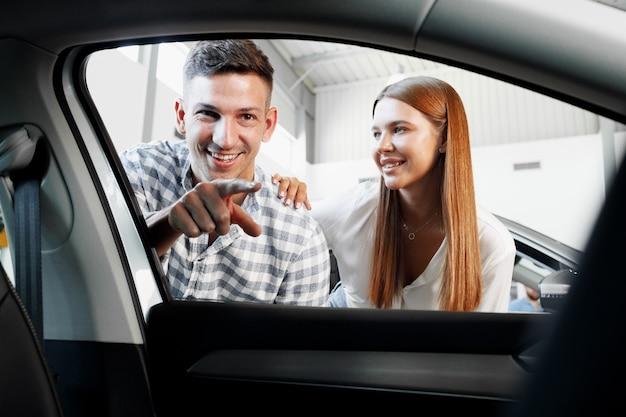 Jeune couple choisissant leur nouvelle voiture dans un magasin de voitures