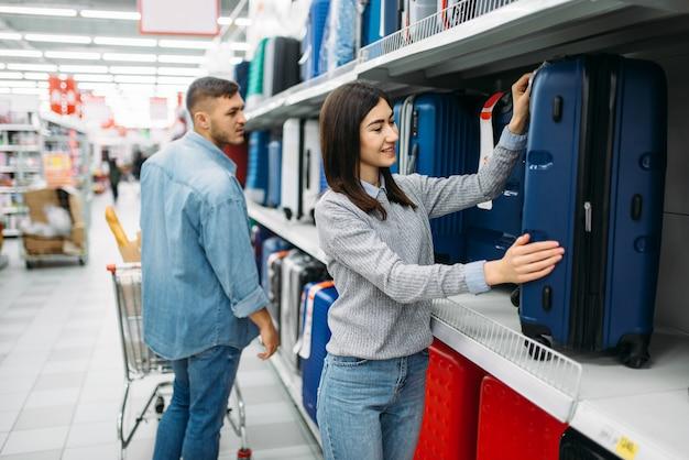 Jeune couple choisissant valise dans un supermarché, shopping familial. clients en boutique, acheteurs en magasin à la recherche de sacs de voyage