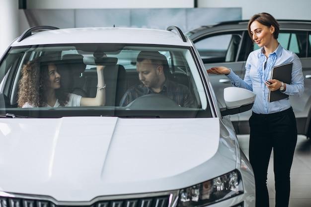 Jeune couple choisissant une voiture dans un salon automobile