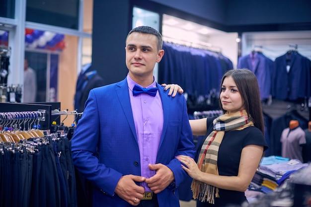 Jeune couple choisit une veste dans le magasin. un mec et une fille aimants achètent des vêtements dans le magasin