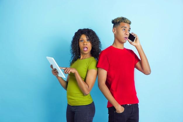 Jeune couple choqué dans des vêtements décontractés posant sur le mur bleu